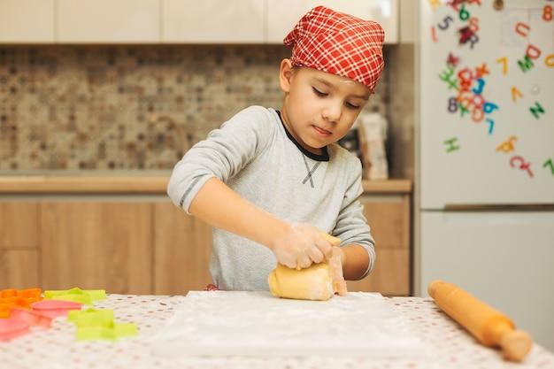 Hermoso niño haciendo masa para galletas