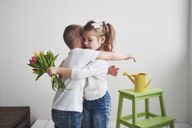 Hermoso niño y niña con tulipanes con abrazo. día de la madre, 8 de marzo, feliz cumpleaños.