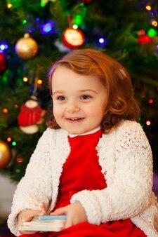 Hermoso niño pequeño cerca de árbol de navidad.