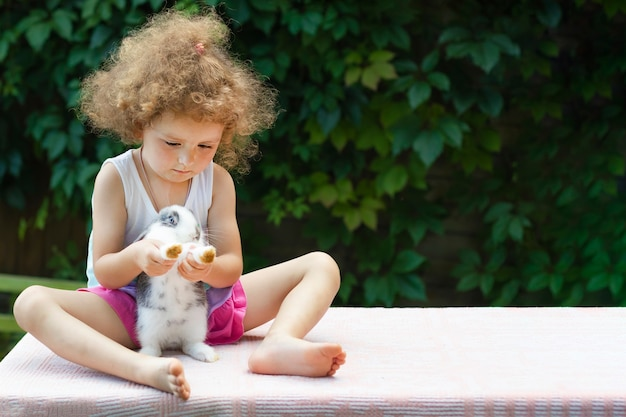 Hermoso niño está sentado y jugando con un conejo
