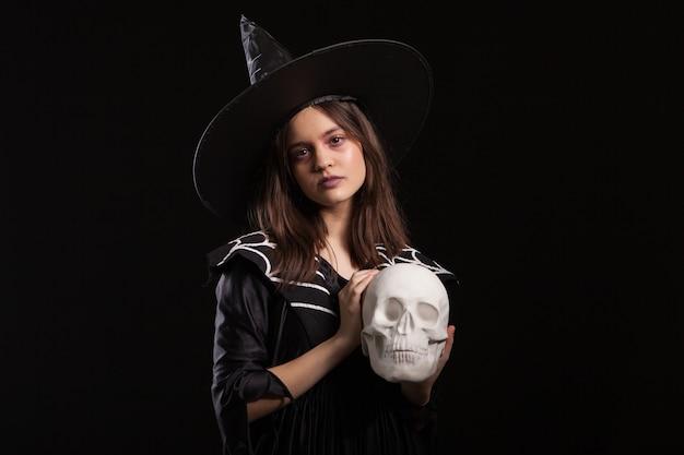 Hermoso niño vestido con un vestido negro para el carnaval de halloween con un cráneo humano en las manos. chica aislada sobre fondo negro con un disfraz de bruja.