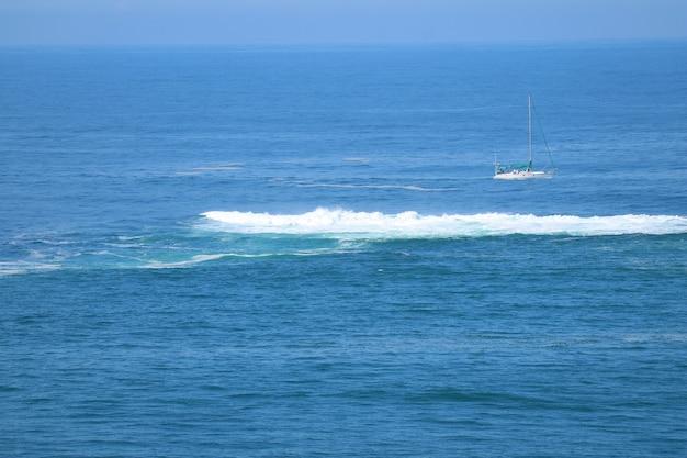 Hermoso océano azul con las olas rompientes y un yate blanco