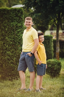 Hermoso padre caucásico posando para la cámara con su pequeño hijo en el parque en verano