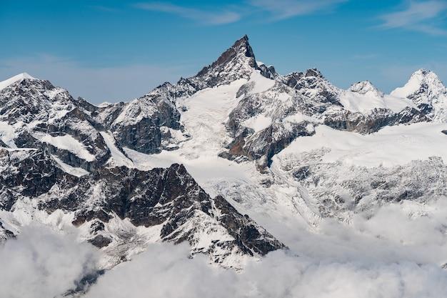 Hermoso paisaje de altas montañas rocosas cubiertas de nieve bajo un cielo azul claro en suiza