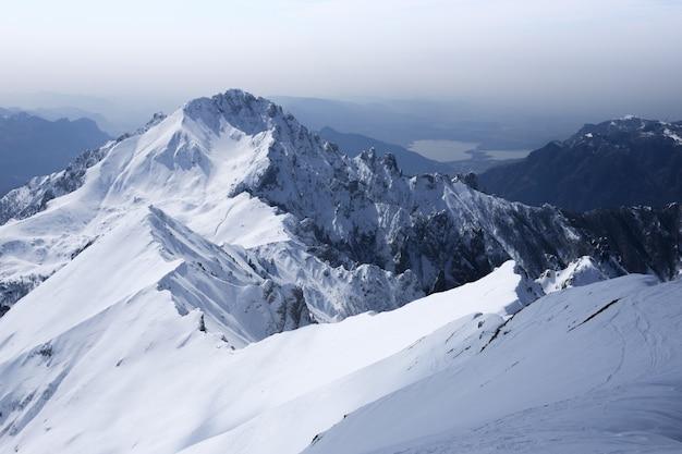 Hermoso paisaje de blancas montañas nevadas y colinas