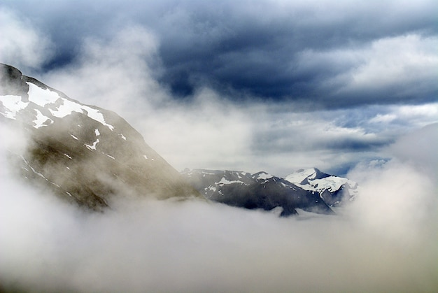 Hermoso paisaje de una cadena montañosa cubierta de nieve bajo nubes blancas en noruega