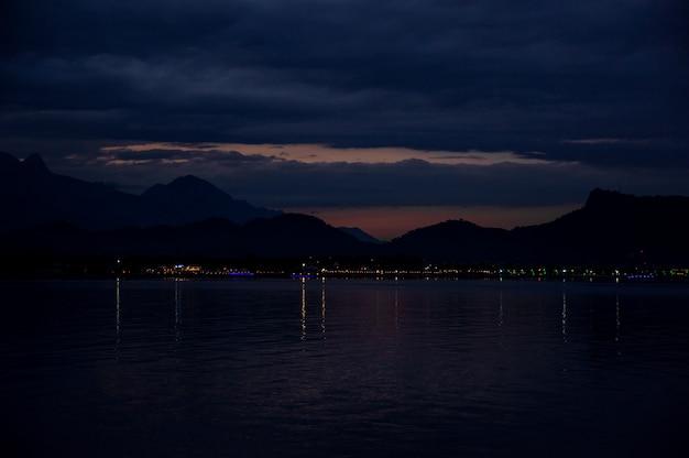 Hermoso paisaje de la ciudad en la playa diferente en la noche al pie de la montaña