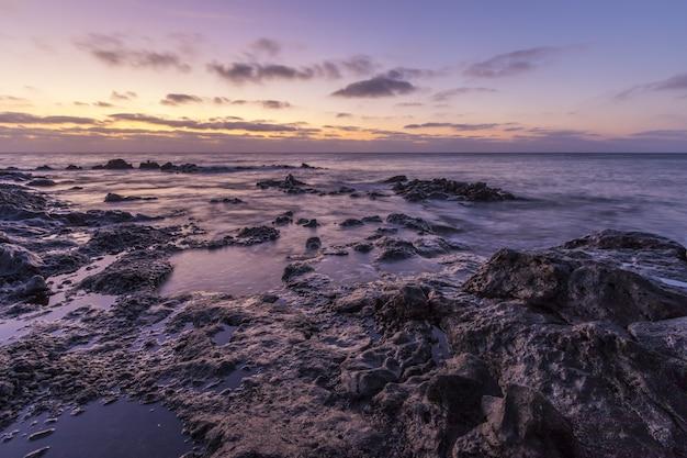 Hermoso paisaje de enormes formaciones rocosas cerca del mar bajo el impresionante cielo del atardecer