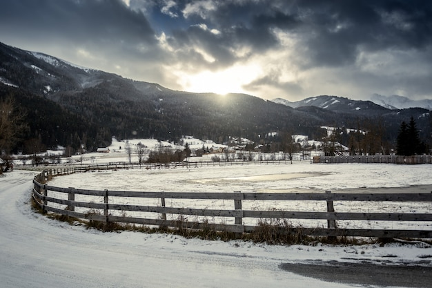 Hermoso paisaje de granja con valla de madera en la ciudad austriaca de las tierras altas al atardecer
