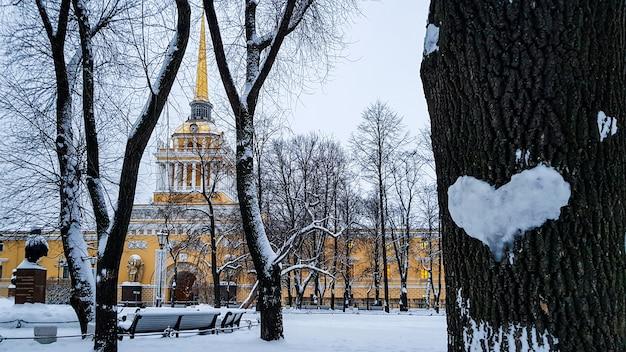 Hermoso paisaje invernal con corazón de nieve en el tronco del árbol y la torre del edificio del almirantazgo, san petersburgo, rusia