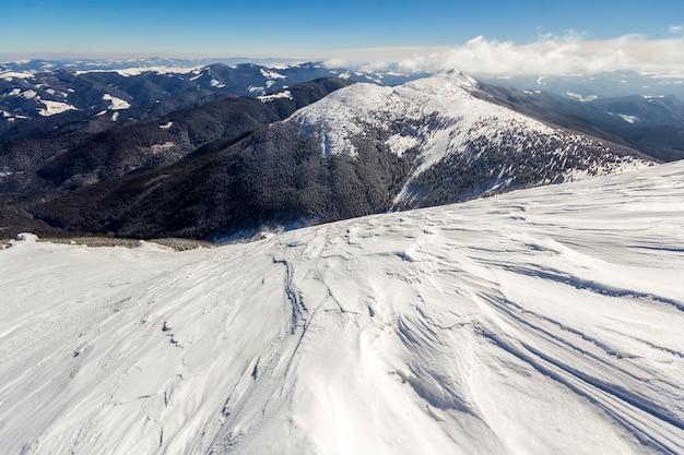 Hermoso paisaje de invierno. ladera empinada de la colina de la montaña con nieve blanca profunda, panorama distante de la cordillera leñosa que se extiende hasta el horizonte y brillantes rayos de sol sobre fondo de cielo azul copia espacio.