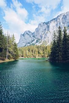 Hermoso paisaje con un lago en un bosque y sorprendentes altas montañas rocosas