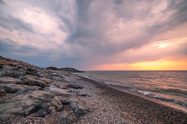Hermoso paisaje magnífico de una costa rocosa, mar y cielo nublado nublado al atardecer