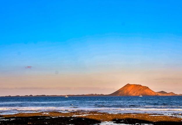 Hermoso paisaje del mar rodeado de colinas durante la puesta de sol