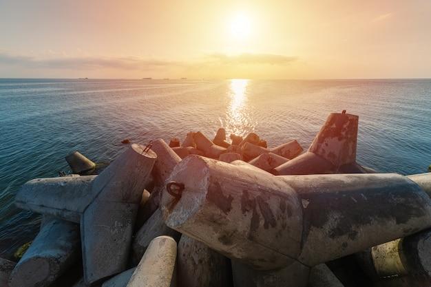 Hermoso paisaje marino al atardecer con concreto para proteger las estructuras costeras de las olas del mar de tormenta