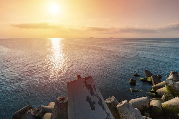 Hermoso paisaje marino al atardecer. viajes de sueños y motivación. rompeolas tetrápodos en la orilla del muelle. buques de carga en el horizonte.