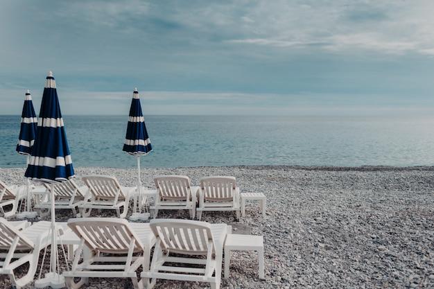 Hermoso paisaje marino con tumbonas y sombrillas. muchas conchas marinas. hermoso día soleado de verano