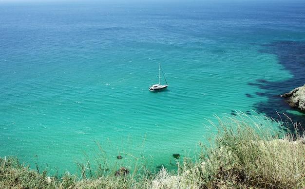 Hermoso paisaje marino con un yate, agua azul transparente y arena blanca.