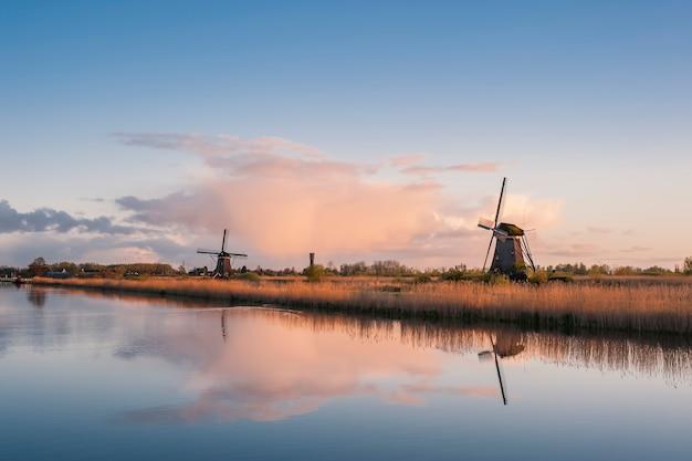 Hermoso paisaje con molinos de viento y majestuoso cielo reflejo en el agua