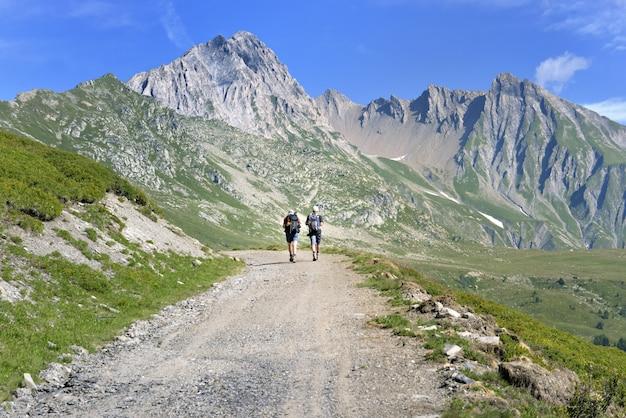 Hermoso paisaje de montaña con excursionistas caminando por una ruta de senderismo