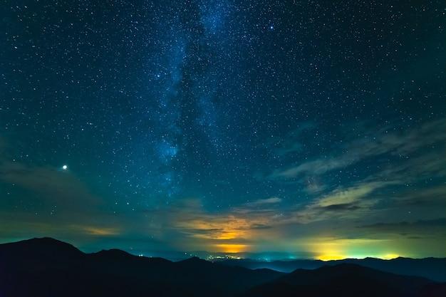 El hermoso paisaje de montaña en el fondo del cielo estrellado.