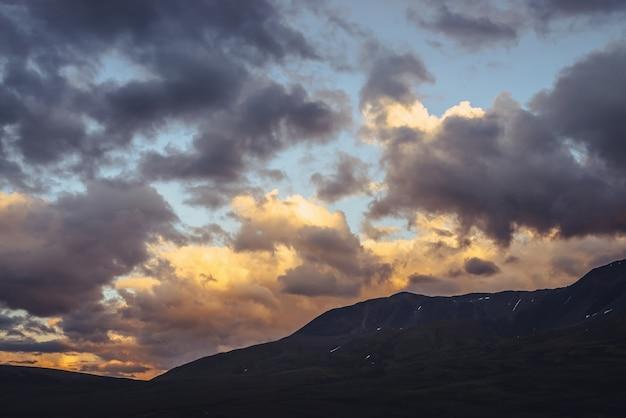 Hermoso paisaje de montaña con luz dorada del amanecer en cielo nublado. pintoresco paisaje de montaña con colores iluminadores en el cielo del atardecer. siluetas de montañas al amanecer. oro iluminando la luz del sol en el cielo