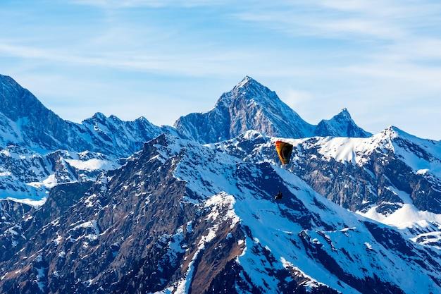 Hermoso paisaje de montañas cubiertas de nieve con un parapente en el tirol del sur, dolomitas, italia