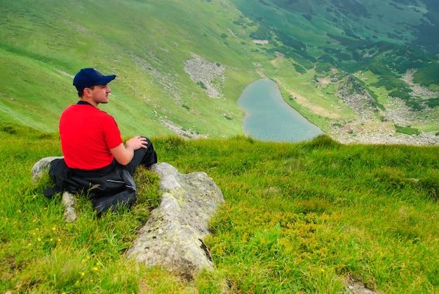 Hermoso paisaje de montañas con lago y nubes en las montañas de los cárpatos y el hombre mira