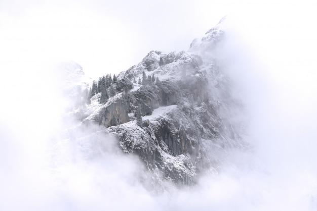 Hermoso paisaje de montañas nevadas y niebla entre picos.