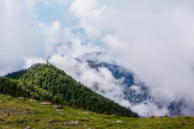 Hermoso paisaje de montañas sobre las nubes