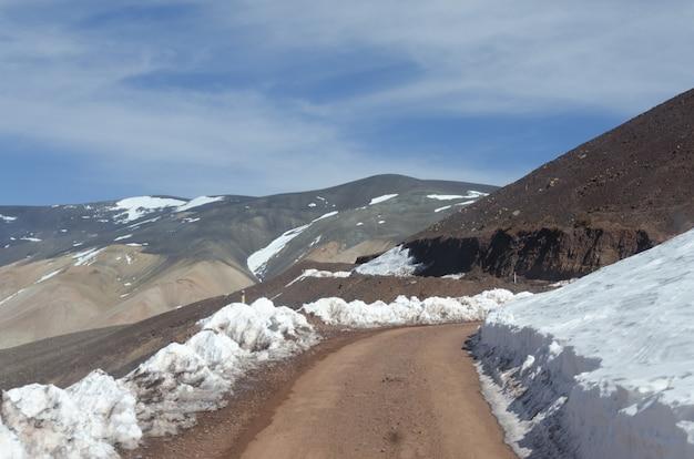 Hermoso paisaje montañoso parcialmente cubierto de nieve bajo un cielo brillante