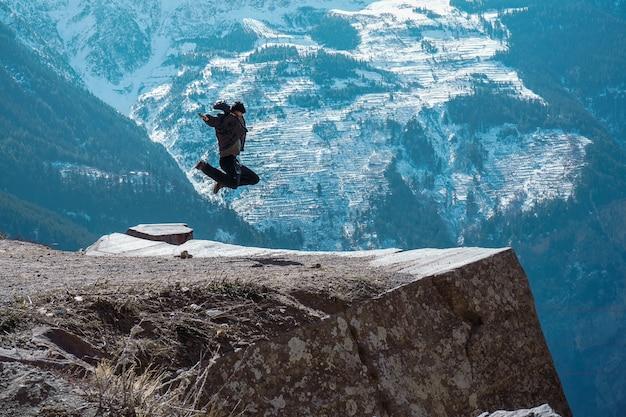 Hermoso paisaje de una mujer saltando en la cima de una montaña rocosa en el punto de suicidio en kalpa