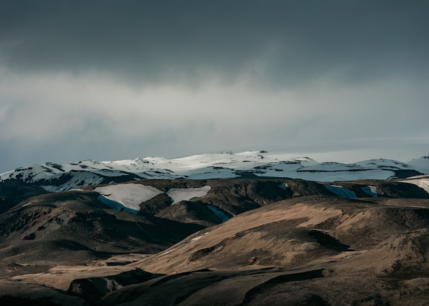 Hermoso paisaje natural con colinas nevadas y cielo gris oscuro