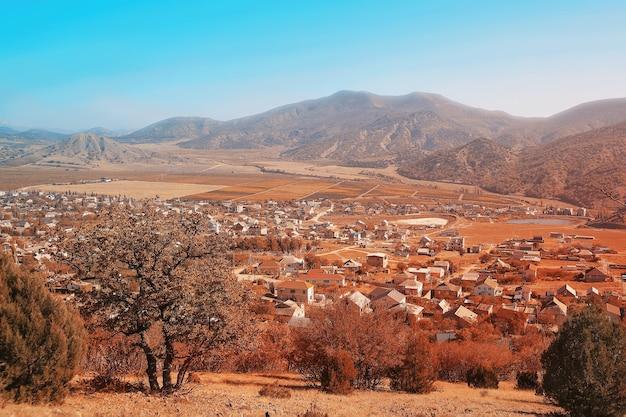 Hermoso paisaje otoñal con vistas a un asentamiento de pequeña ciudad con montañas y cielo azul