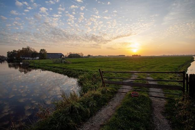 Hermoso paisaje de un paisaje de pólder holandés durante la puesta de sol