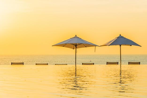 Hermoso paisaje de piscina al aire libre con sombrilla y tumbona en el hotel resort para relajarse tra