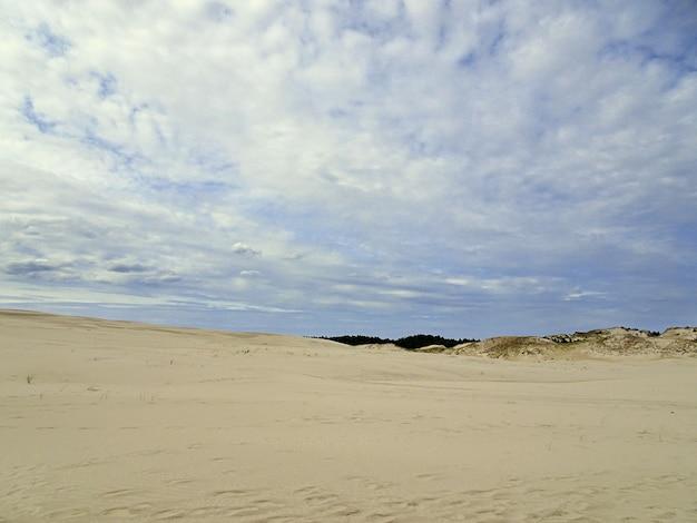 Hermoso paisaje de una playa de arena bajo un cielo nublado en leba, polonia