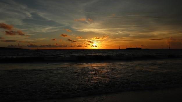 Hermoso paisaje en la playa con puesta de sol y nubes en bali, indonesia