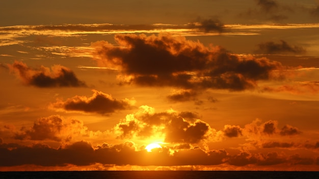 Hermoso paisaje en la playa con puesta de sol y nubes