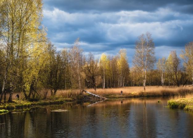 Hermoso paisaje de primavera con pescadores y reflejos de árboles en el lago