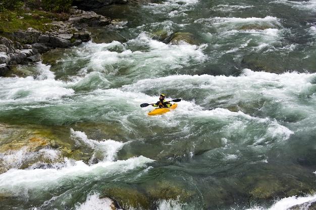 Hermoso paisaje del rafting en la corriente del río de montaña que fluye hacia abajo entre enormes piedras