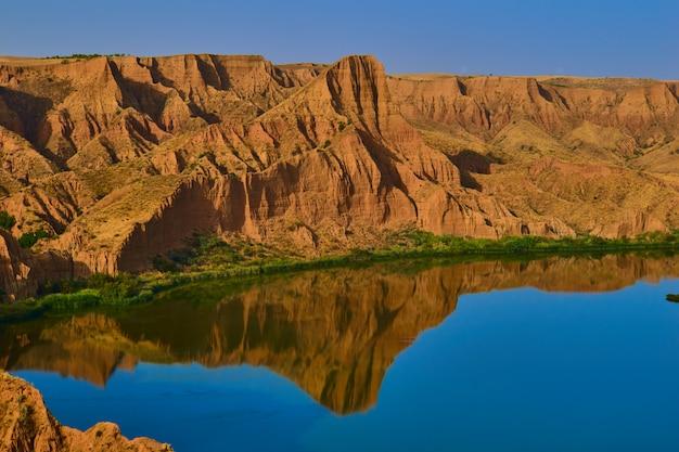 Hermoso paisaje con rocas rojas y lago en primer plano con reflejo en el agua, toledo, españa