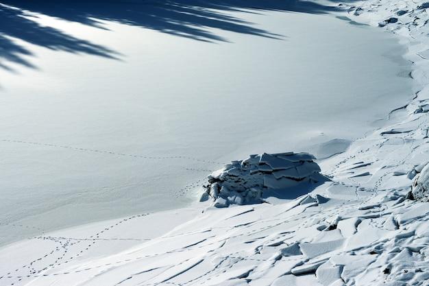 Hermoso paisaje de tierra cubierta de nieve con grietas en los dolomitas