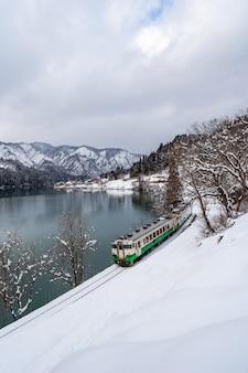 Hermoso paisaje del tren de la línea tadami a través del río tadami en invierno en fukushima, japón