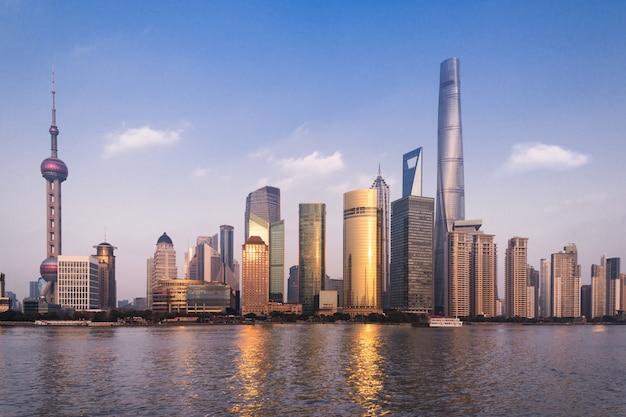 Hermoso paisaje urbano con rascacielos de cristal de pie junto al río con el telón de fondo del sol poniente