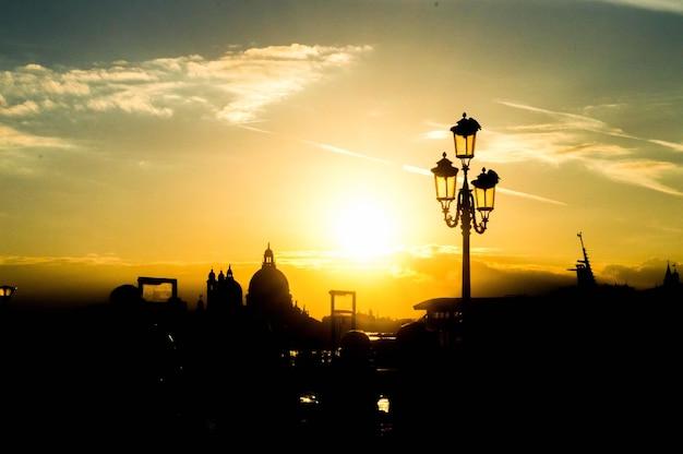 Hermoso paisaje urbano con siluetas de una farola y edificios en la puesta de sol
