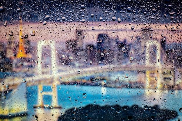 Hermoso paisaje vista conceptual de la ciudad a través de la ventana de vidrio con gotas de lluvia