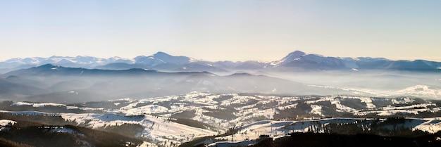 Hermoso panorama de invierno con nieve fresca. paisaje con pinos abetos, cielo azul con luz solar y altas montañas de los cárpatos de fondo.
