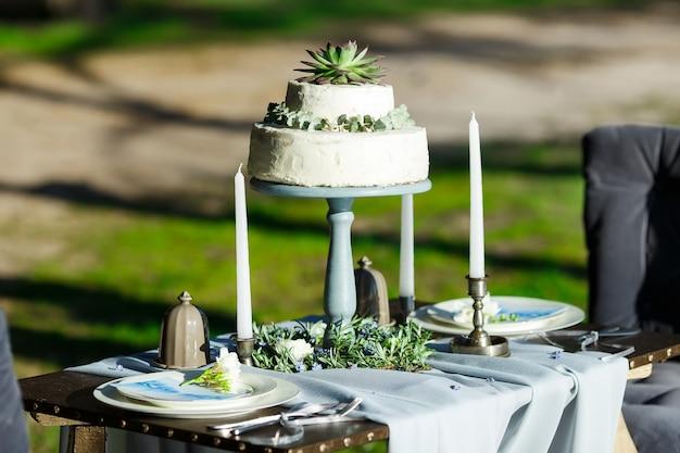 Hermoso pastel de bodas blanco con flores al aire libre