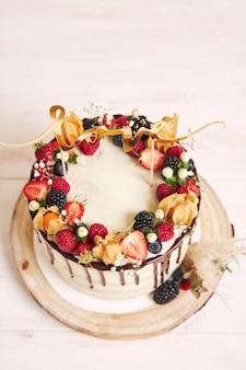 Hermoso pastel de bodas con frutas, goteo de chocolate y con cartas de amor